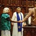 Catholic priest leading in Lord's prayer